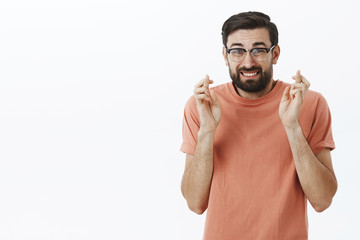 Hope everything goes on plan. Faithful and concerned insecure cute guy in glasses with beard grimacing unsure as cross fingers for good luck, making wish to desire come true, worry over gray wall