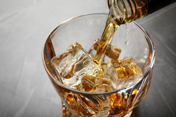 Pouring whiskey from bottle into glass with ice cubes on table, closeup