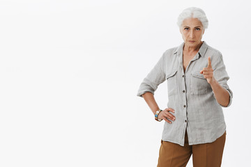 I worn you young lady. Serious-looking displeased and angry grandmother with gray hair pointing at camera with index finger looking from under forehead threatening with punishment or scolding