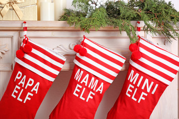 Red Christmas stockings hanging on decorated fireplace, indoors. Festive interior