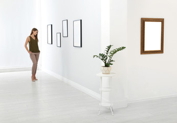 Young woman viewing exposition in modern art gallery