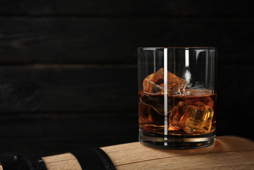 Golden whiskey in glass with ice cubes on wooden barrel. Space for text
