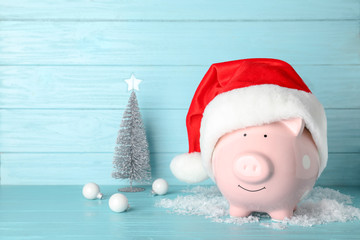 Composition with piggy bank and Christmas decor on table. Space for text