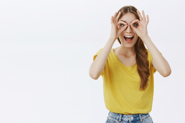 Waist-up shot of funny excited and creative happy caucasian girl with braid in yellow t-shirt making circles over eyes as if looking throught goggles smiling amazed feeling surprised and enthusiastic