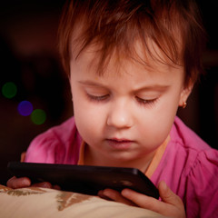 Social networks, friendship, technology and children concept. Portrait of sleepy little child girl using cellphone on the bed.