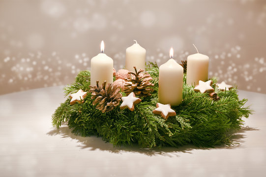 Second Advent - decorated Advent wreath from fir and evergreen branches with white burning candles, tradition in the time before Christmas, warm background with festive bokeh and copy space