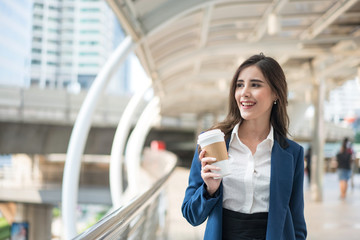 Beautiful Woman Going To Work With Coffee Walking Near Office Building. Portrait Of Successful Business Woman Holding Cup Of Hot Drink In Hand On Her Way To Work On City Street