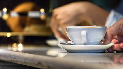 Man waiter hand serving on the counter a cappuccino cup in a coffee shop, Italy.