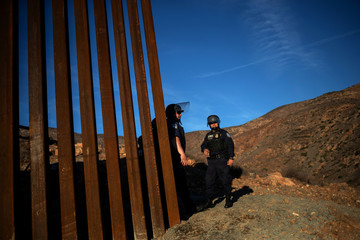 CBP officials stand watch at border wall with Mexico as photographed from the outskirts of Tijuana, Mexico