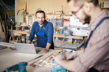 Portrait of mature bearded carpenter talking to apprentice while working in modern joinery, copy space