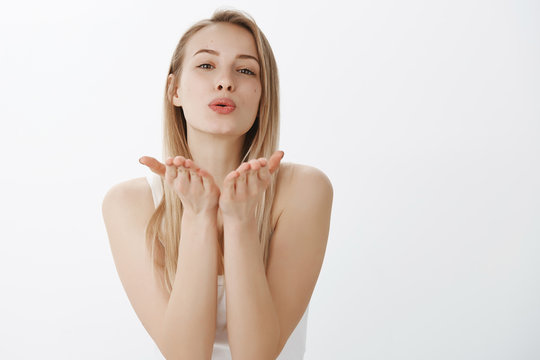 Passionate and loving good-looking tender girlfriend with blond hair tilting forward as folding lips and raising hands near mouth to send air kiss at camera posing coquettish and flirty over gray wall