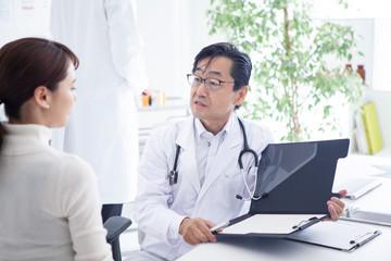 診察室で問診内容をカルテに記入する男性医師