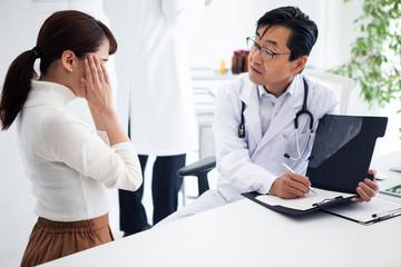 頭痛のため病院に来た女性と診察をする医師