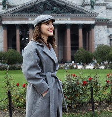 Outdoor photo of fashionable female model with hat walking around city in autumn vacation.