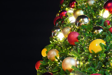 Closeup of red and colorful bauble hanging from a decorated Christmas tree