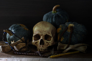 Skull with bone and thai pumpkins whis has old beads put on old table