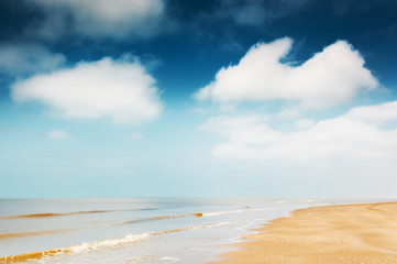 Beautiful sandy beach and the blue sky with white clouds. Sea coast in Noordwijk, Netherlands, Europe