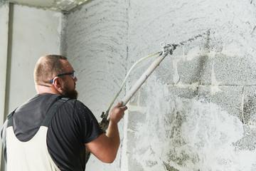 Plasterer using screeder spraying putty plaster mortar on wall