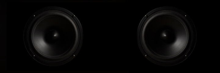Black Music speaker on a black isolated background. Concept of party or listening to music. Banner