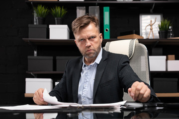 Businessman sitting at computer table and tears document