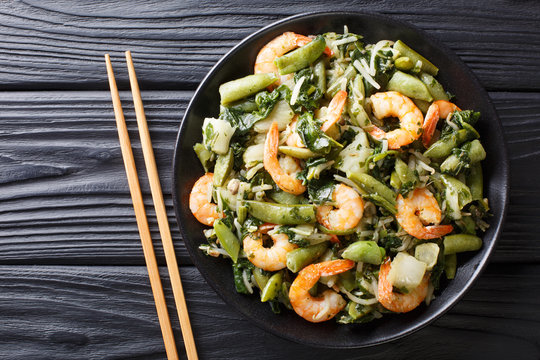 Delicious peeled king prawns with a refreshing mix of pak choi, spinach, soy beans and sugar snap peas closeup. horizontal top view