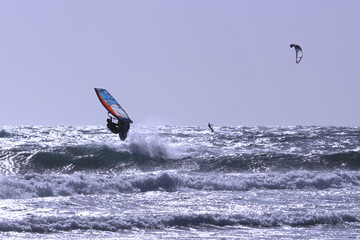 Jumping windsurfer and kite-surfer in the distance on the Atlantic ocean