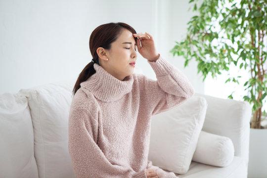 自宅で頭痛と発熱に悩む女性