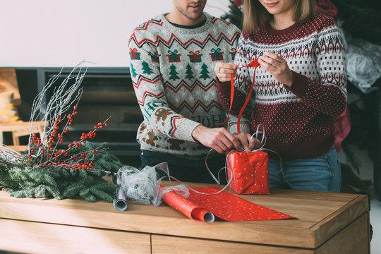 Woman and man wrapping Christmas presents