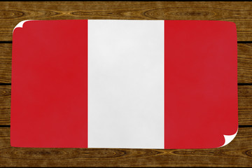 Illustration of a Peruvian flag on the paper pasted on the woody wall