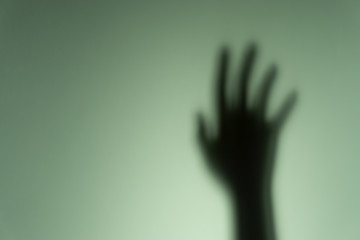 Blurry shadow of the hand on wall background. Safety and motivation concept