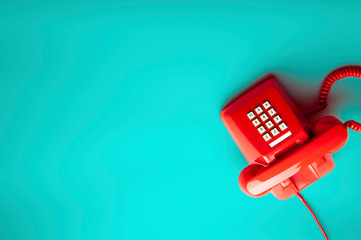 top view of vintage red telephone on green background