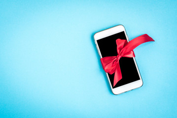 Mobile phone with red bow on blue background.