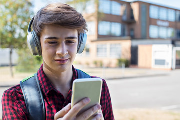 Male Teenage Student Outside College Building Streaming Music From Mobile Phone To Wireless Headphones