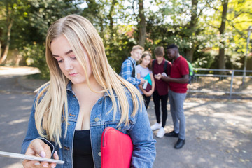 Unhappy Teenage Girl Being Bullied By Text Message At School