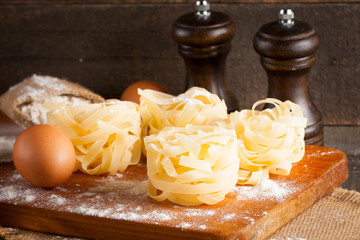 Closeup of raw homemade pasta with ingredients on wooden, rustic background. Pasta, salt, eggs, yolk, pepper. Home made food concept.