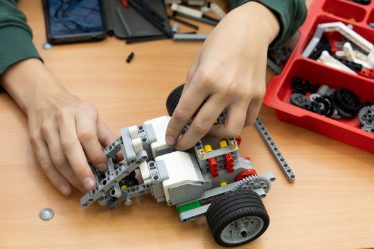 Verkhnyaya Physhma/Russia- November, 2018. Close up of child hands constructing  a robot. Robotics class for child and teen. Science at school.