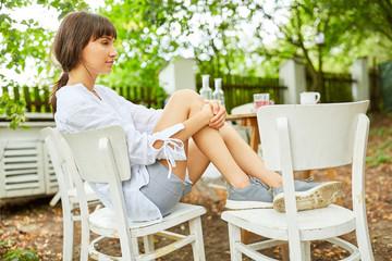 Junge Frau sitzt am Gartentisch