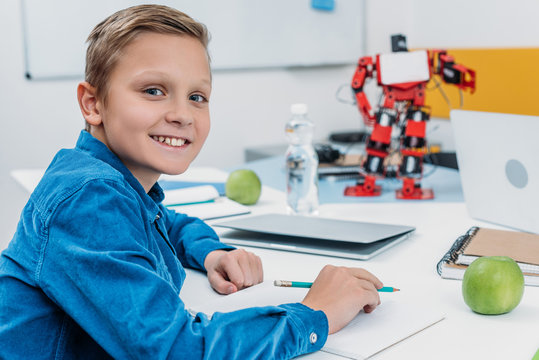 schoolboy sitting at desk with robot model, looking at camera and writing in notebook during STEM lesson