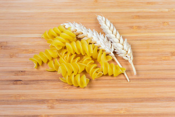 Uncooked fusilli pasta and wheat ears closeup on wooden surface
