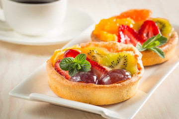 Photo of a fruit and berry tart dessert with toss sugar on wooden background. Fresh delicious sweet cake with raspberries, grapes, strawberries, cherry, kiwi, grapefruit and cream.
