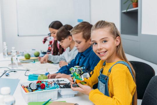 cheerful classmates making a robot during STEM robotics class