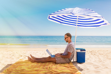 Young man with laptop working on the sand beach under umbrella on sea cost.