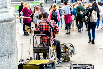 Melbourne, Victoria, Australia, May 26th 2018: A solo busker is sitting in front of the Flinders Street Train Station