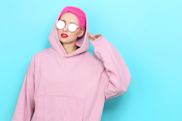Fashion portrait of young hipster woman in pink hoody. Short pink hair