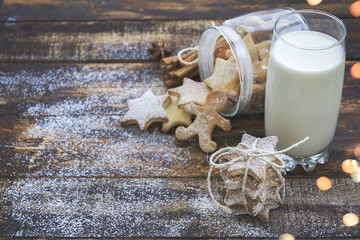 Glass of milk and christmas cookies on brown wooden background with christmas lights