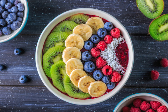 Healthy breakfast with delicious acai smoothie in bowl on dark background