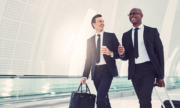 Smiling businessmen talking together while walking in an airport