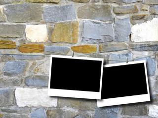 Two blank rectangular instant photo frames against multicolored stone wall background