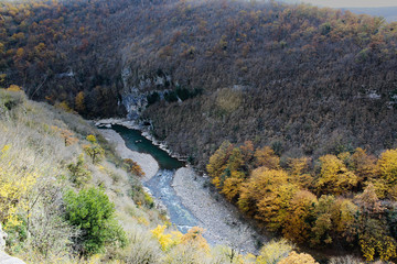 River bends through a colorful autumn forest surrounded by high mountains