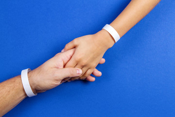 Mockup template blank paper wristband, bracelet on man and kid arms, blue color background